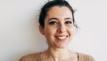 Junge Frau freut sich über Zahnersatz in einer Sitzung in Innsbruck.