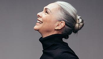 Frau freut sich, dass die Parodontitisbehandlung so schonend war.