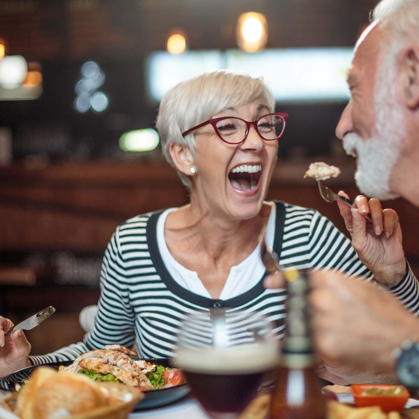 """Ehepaar lacht nach der Behandlung """"Feste Zähne an einem Tag"""" glücklich und zufrieden mit festsitzendem Zahnersatz."""
