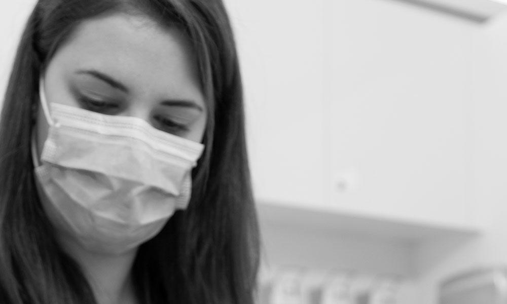 Mitarbeiterin schaut konzentriert bei der Oralchirurgie in Innsbruck.