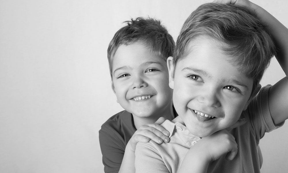 Zwei jungen lachen dank Zahnprophylaxe in Innsbruck mit gesunden Zähnen.