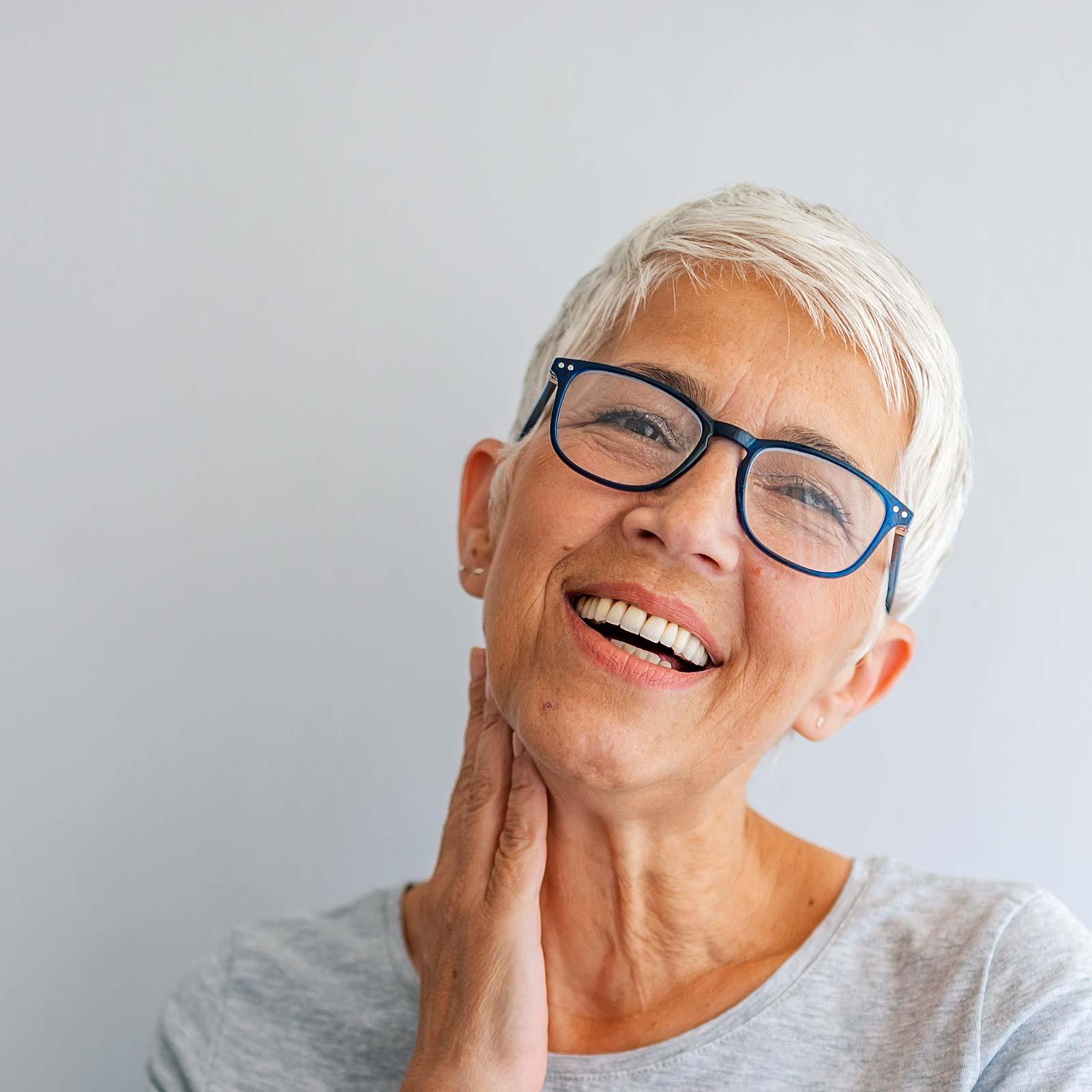 Frau im besten Alter freut sich über Zahnersatz aus Innsbruck.