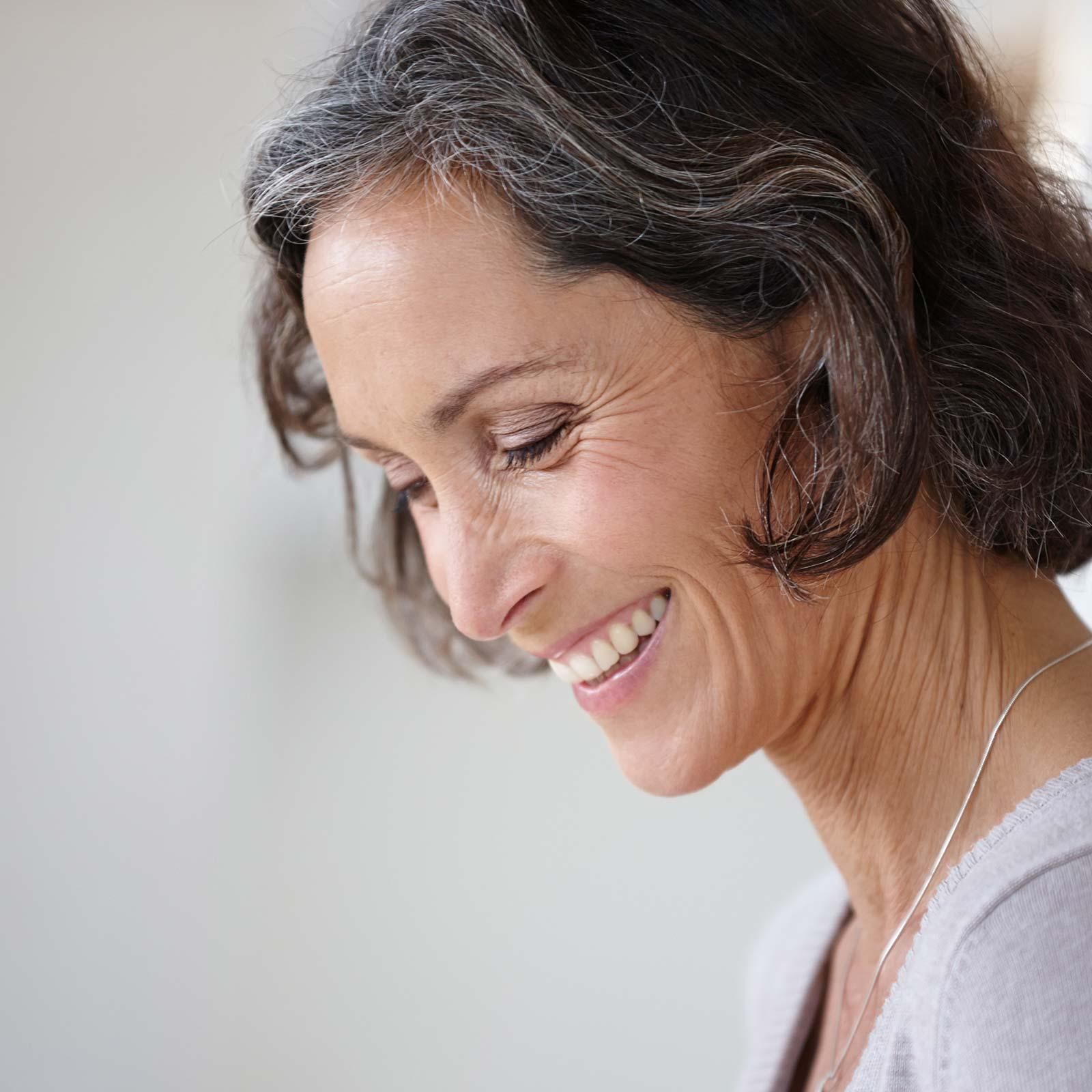 Frau ist glücklich, weil ihre Wurzelbehandlung in Innsbruck so schonend war.